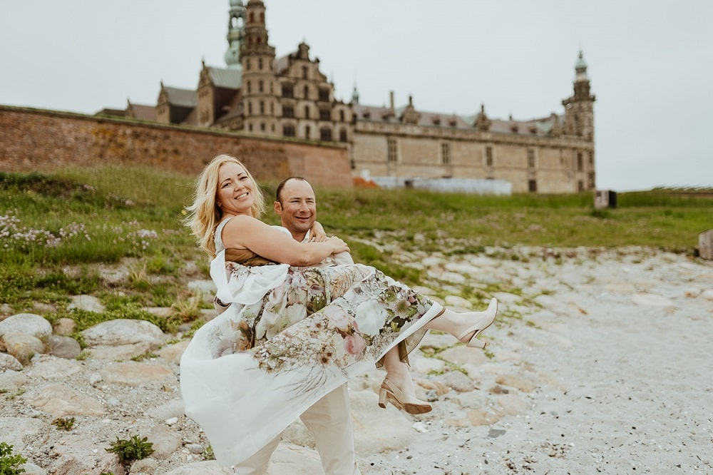 A couple in the front of Danish castle of Hamlet - See the Small Wedding Abroad Ideas from Nordic Adventure Weddings